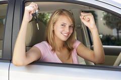 庆祝的十几岁的女孩拥有第一辆汽车 免版税库存照片