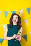 年轻庆祝的妇女绿色礼服,拿着一杯香槟 免版税库存图片