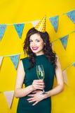 年轻庆祝的妇女绿色礼服,拿着一杯香槟 免版税库存照片
