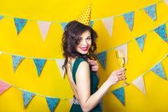 年轻庆祝的妇女绿色礼服,拿着一杯香槟 库存图片