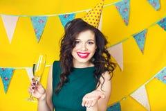 年轻庆祝的妇女绿色礼服,拿着一杯香槟 免版税图库摄影