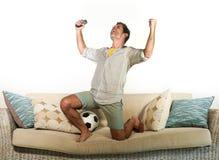 庆祝目标疯狂愉快在家跳跃在沙发长沙发的年轻热心足球迷观看在电视上的足球赛举行 库存图片