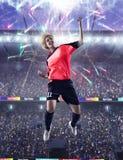 庆祝目标的女性足球运动员 免版税库存图片
