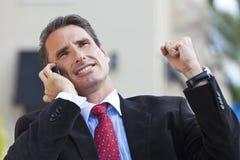 庆祝移动电话成功的生意人 免版税图库摄影