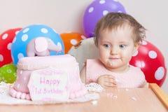 庆祝第一个生日和吃蛋糕的滑稽的婴孩 图库摄影