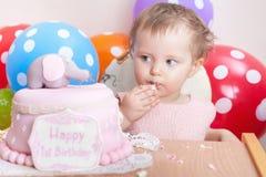 庆祝第一个生日和吃蛋糕的滑稽的婴孩 库存照片