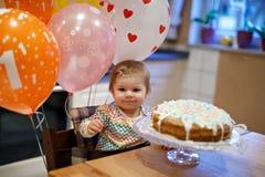 庆祝第一个生日的可爱的矮小的女婴 吃在自创蛋糕的婴孩marshmellows装饰,室内 库存图片