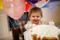 庆祝第一个生日的可爱的矮小的女婴 吃在自创蛋糕的婴孩marshmellows装饰,室内 库存照片