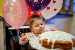 庆祝第一个生日的可爱的矮小的女婴 吃在自创蛋糕的婴孩marshmellows装饰,室内 免版税库存照片