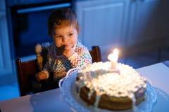 庆祝第一个生日的可爱的矮小的女婴 吹在自创被烘烤的蛋糕的孩子一个蜡烛,室内 库存图片