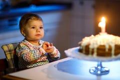 庆祝第一个生日的可爱的矮小的女婴 吹在自创被烘烤的蛋糕的孩子一个蜡烛,室内 图库摄影
