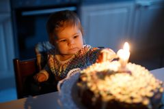 庆祝第一个生日的可爱的矮小的女婴 吹在自创被烘烤的蛋糕的孩子一个蜡烛,室内 免版税图库摄影