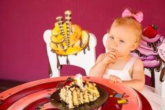庆祝第一个生日的小愉快的女婴 孩子和她的第一个蛋糕在党 童年 免版税库存照片