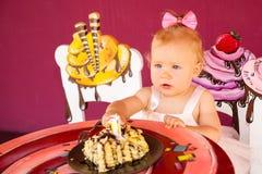 庆祝第一个生日的小愉快的女婴 孩子和她的第一个蛋糕在党 童年 免版税库存图片