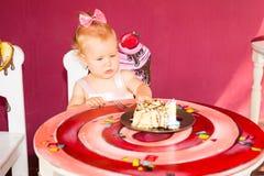 庆祝第一个生日的小愉快的女婴 孩子和她的第一个蛋糕在党 童年 图库摄影