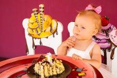 庆祝第一个生日的小愉快的女婴 孩子和她的第一个蛋糕在党 童年 库存照片