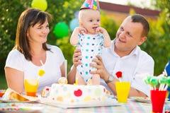 庆祝第一个生日婴孩的愉快的家庭 免版税库存照片