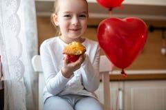 庆祝第6个生日的逗人喜爱的学龄前儿童女孩 吃她的生日杯形蛋糕的女孩在厨房里 免版税库存图片