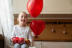 庆祝第6个生日的逗人喜爱的学龄前儿童女孩 拿着她的生日杯形蛋糕和美妙地被包裹的礼物的女孩 库存照片