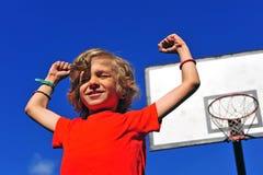 庆祝胜利用他的手的愉快的微笑的男孩 图库摄影