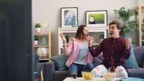 庆祝胜利的男人和妇女拥抱和笑在电视的体育比赛以后 股票视频