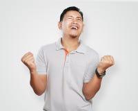 庆祝胜利的滑稽的年轻亚裔人 免版税库存照片