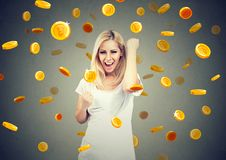 庆祝财政成功的一个愉快的少妇的画象在bitcoin雨下 图库摄影