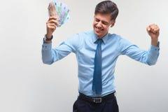 庆祝货币收入的商人反对白色背景 免版税库存照片