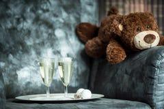 庆祝-玩具熊和两杯在一块白色板材的香槟在有书的一把扶手椅子 库存图片