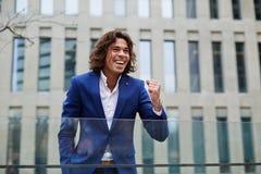 庆祝他的成功的年轻商业主管站立户外 库存照片