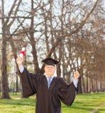庆祝他的毕业的成熟人在公园 库存照片