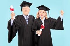 庆祝他们的毕业的成熟人民 免版税库存照片