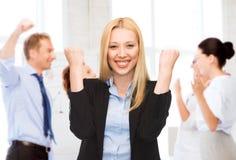 庆祝succes的女实业家在办公室 免版税库存照片