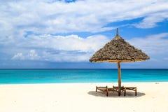 床和伞在白色沙子靠岸 免版税库存照片