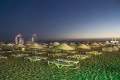 床和秸杆伞在一个海滩在晚上 免版税库存照片