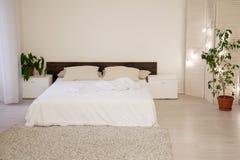 床和绿色植物在白色卧室 库存照片