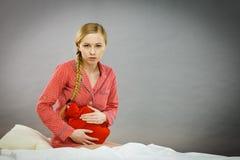 床感觉痛苦的哀伤的年轻少年妇女 免版税图库摄影