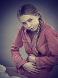 床感觉痛苦的哀伤的年轻少年妇女 库存照片
