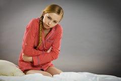 床感觉痛苦的哀伤的年轻少年妇女 免版税库存照片