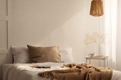 床特写镜头与米黄毯子和亚麻制枕头的在最小的卧室内部,真正的照片 库存图片