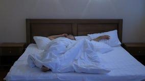 床覆盖物的年轻人他的头和耳朵有枕头的,因为他不要醒,遭受喧闹的警报  股票视频