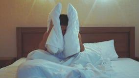 床覆盖物的年轻人他的头和耳朵有枕头的,因为他不要醒,遭受喧闹的警报  股票录像