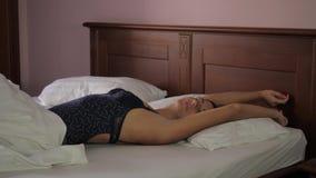 床谎言的被晒黑的妇女浅黑肤色的男人在毯子、拉扯它和舒展下 股票录像