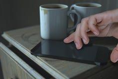 床头柜和手机 免版税库存照片