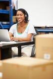 仓库佩带的耳机和使用膝上型计算机的工作者 免版税图库摄影