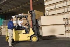 仓库保管员和叉架起货车司机在木材工厂 免版税库存照片