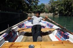 库尔德男孩在Urfa荡桨一条小船在土耳其 免版税库存照片