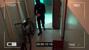 库尔斯克,俄罗斯, 6月30日:监视器捉住了窃贼打破了门并且窃取了自行车 股票录像