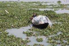 库尔纳,孟加拉国, 2017年2月28日:与一条小木小船的人划船 免版税库存照片