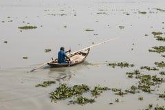 库尔纳,孟加拉国, 2017年2月28日:与一条小木小船的人划船 库存图片